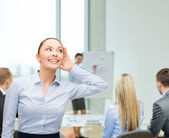 Smiling businesswoman listening gossig — Stock Photo