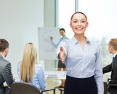 Businesswoman with opened hand ready for handshake — Stock Photo