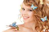 Happy teenage girl with butterflies in hair — Stock Photo