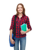 Smiling female student with bag and notebooks — ストック写真