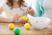 Close up of little girl and mother coloring eggs — Stockfoto