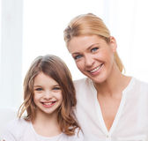 Smiling mother and little girl with laptop at home — Stock Photo