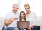 Parents and girl with laptop and credit card — Stock Photo
