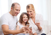 Parents and little girl with smartphones at home — Stock Photo