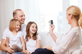 Mother taking picture of father and daughters — Stock Photo