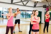 Group of smiling people stretching in the gym — Stock Photo