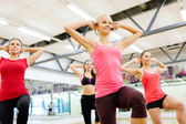 Group of smiling femalewith trainer exercising — Stock Photo