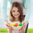 Smiling girl and mother holding colored eggs — Stock Photo #42854287