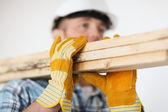 Close up of male in gloves carrying wooden boards — Fotografia Stock