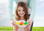 Smiling girl and mother holding colored eggs — Stock Photo