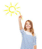 Cute little girl drawing sun with brush — Stock Photo