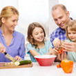 Happy family with two kids making dinner at home — Stock Photo