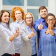 Happy creative team showing thumbs up in office — Stock Photo