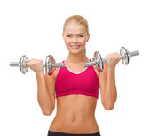 Smiling woman lifting steel dumbbells — Stock Photo