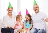 Happy family with two kids in hats celebrating — Stock Photo