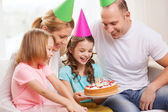 Smiling family with two kids in hats with cake — Stock Photo