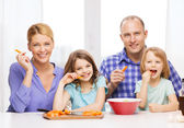 Happy family with two kids eating at home — Stok fotoğraf
