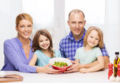 Happy family with two kids with salad at home — Stok fotoğraf