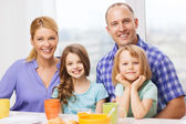 Happy family with two kids with having breakfast — Stockfoto
