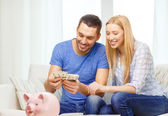 Smiling couple counting money at home — Stock Photo