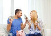 돈과 piggybank ot 테이블 집에서 커플 — Stok fotoğraf