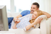 Smiling couple watching movie at home — Stock Photo
