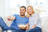 Smiling couple with popcorn watching movie at home — Stock Photo