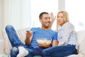 Smiling couple with popcorn choosing what to watch — Stock Photo
