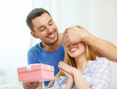 Smiling man surprises his girlfriend with present — Stock fotografie