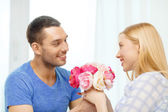 Smiling man giving girfriens flowers at home — Stock Photo