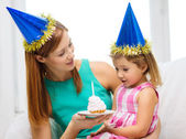 Mother and daughter in blue hats with cake — Photo