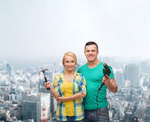 Smiling couple with hammer and drill — Stock Photo
