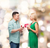 Smiling couple with flower bouquet and ring — Stock Photo