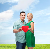 Smiling couple holding big red heart — Photo