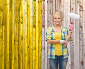 Smiling woman in gloves with paint roller — Stockfoto