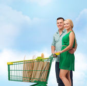 Smiling couple with shopping cart and food in it — Stock fotografie