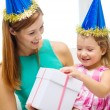 Mother and daughter in blue hats with gift box — Stock Photo