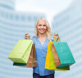 Smiling woman with many shopping bags — Photo