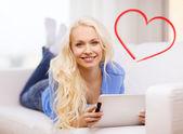 Mulher sorridente com computador do tablet pc em casa — Fotografia Stock