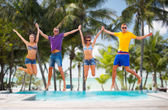 Group of friends or couples jumping on the beach — Stock Photo