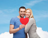 Smiling couple holding big red heart — Stock fotografie