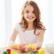Smiling little girl coloring eggs for easter — Stock Photo #43020231