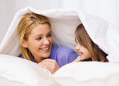 Mother and little girl under blanket at home — Photo