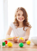 Smiling little girl coloring eggs for easter — Stock Photo