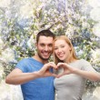 Smiling couple showing heart with hands — Stock Photo