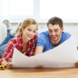 Smiling couple looking at blueprint at home — Stock Photo #43054073