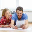 Smiling couple looking at tablet pc at home — Stock Photo #43054139