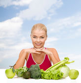 Smiling sporty woman with organic food — Stockfoto