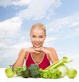 Sonriente mujer deportiva con alimentos orgánicos — Foto de Stock