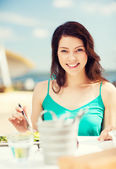 Girl eating in cafe on the beach — Photo